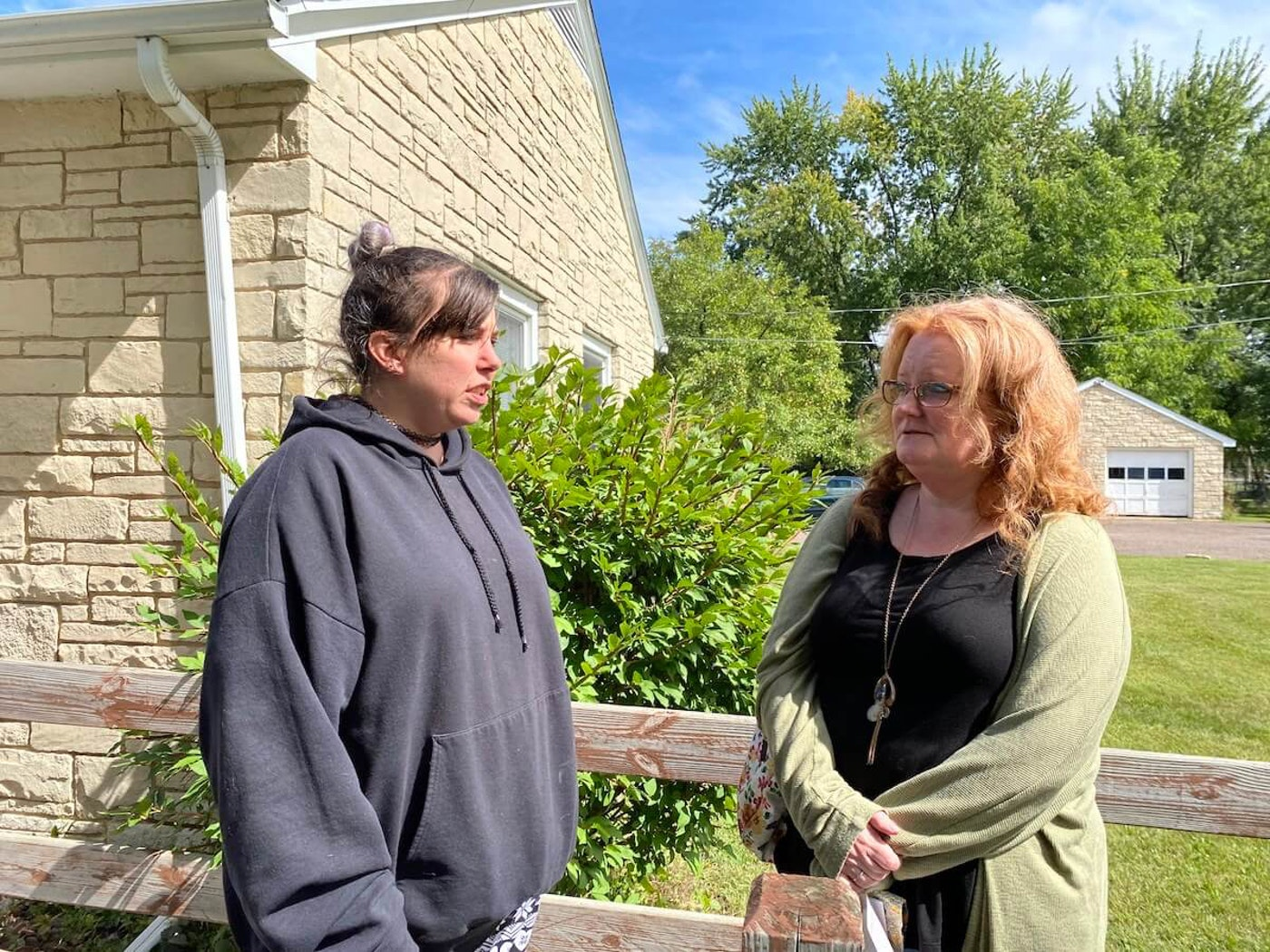 Nikki Hays, left, who lives at the Reality Unlimited group home in Eau Claire, talks Thursday with group home owner Audrey Nelson. (Photo by Julian Emerson).