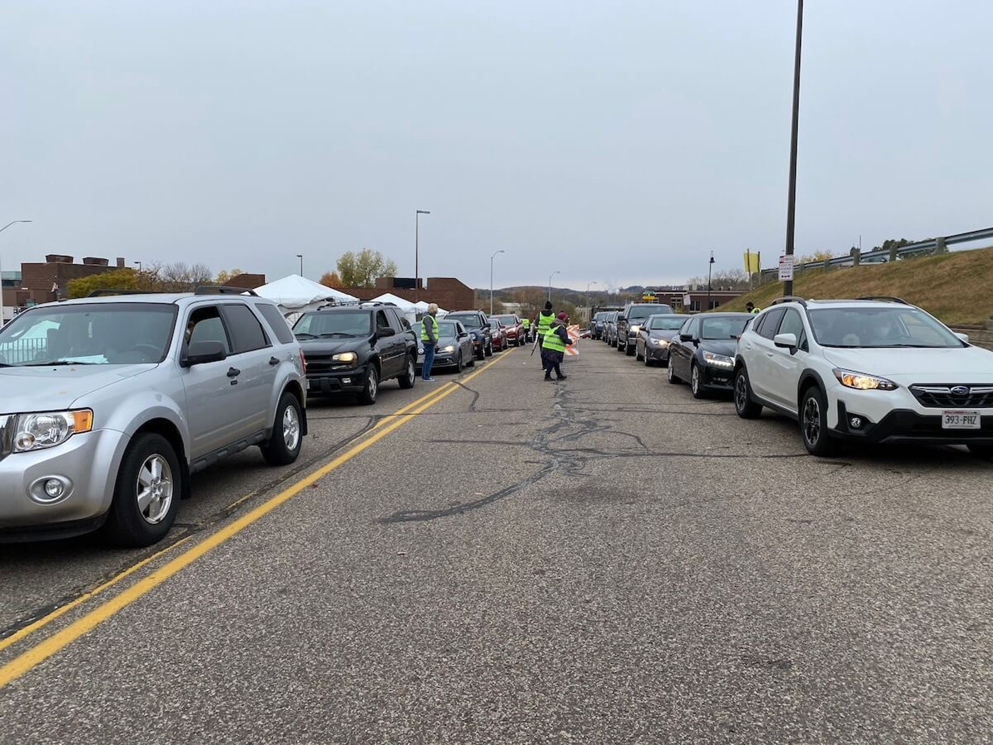 Dozens of vehicles line South Dewey Street near City Hall in Eau Claire as motorists cast ballots on the first day of early in-person voting in Wisconsin for the Nov. 3 election. (Photo by Julian Emerson)