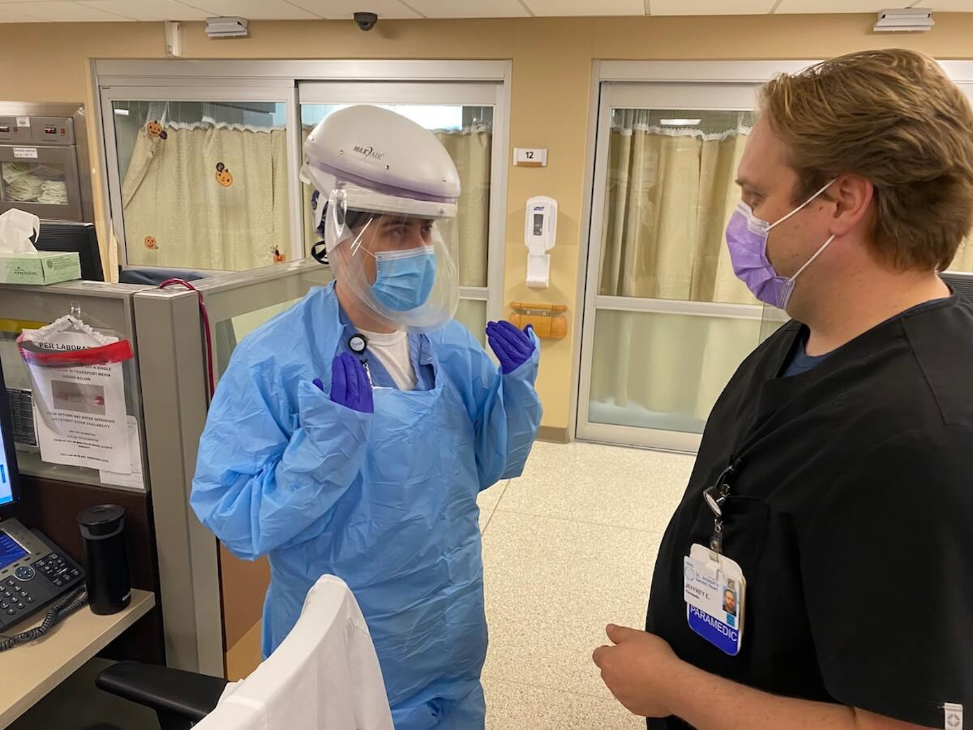 Tyler Bowe, left, an emergency room nurse at HSHS Sacred Heart Hospital in Eau Claire, talks with Jeffrey Ellenbecker, a paramedic at the hospital, before he enters the room of a COVID-19 patient Wednesday. (Photo provided by HSHS Sacred Heart Hospital)