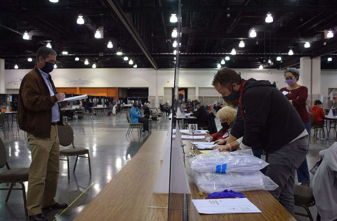 At left, Bill Bridge, a Trump-supporting recount observer, watches election officials work Friday at the Wisconsin Center in Milwaukee. (Photo by Jonathon Sadowski)