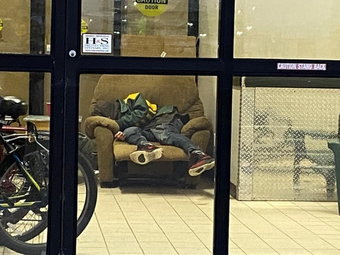 A homeless man sleeps in a chair Sunday evening in the entrance to Sojourner House homeless shelter in Eau Claire. Continued coronavirus outbreaks among people who stay at the shelter and staff who work there are prompting concerns about whether the shelter will remain open this winter. (Photo by Julian Emerson)