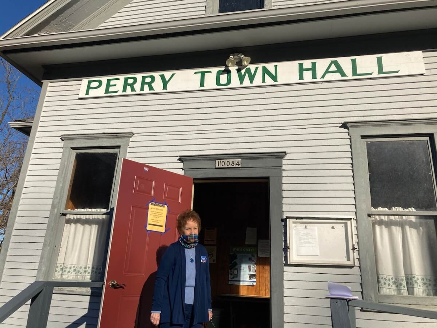 Clerk Mary Price stands outside the 109-year-old Perry Town Hall. Located in a rural corner of Dane County, Wis., its population is 670. (Photo by Susan Lampert Smith)