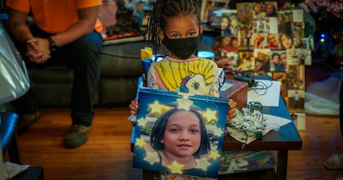 Anija Ragland, 6, holds a portrait of sister, Anisa Scott, on Dec. 1. Since Anisa's death on Aug. 13, the portrait goes everywhere the family goes. (Photo © Andy Manis)