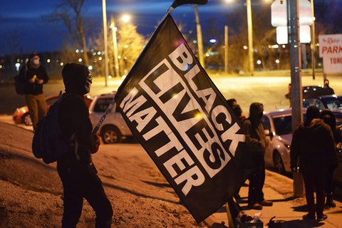 A protester holds a Black Lives Matter flag Monday, Dec. 14, 2020 in Milwaukee. (Photo by Jonathon Sadowski)