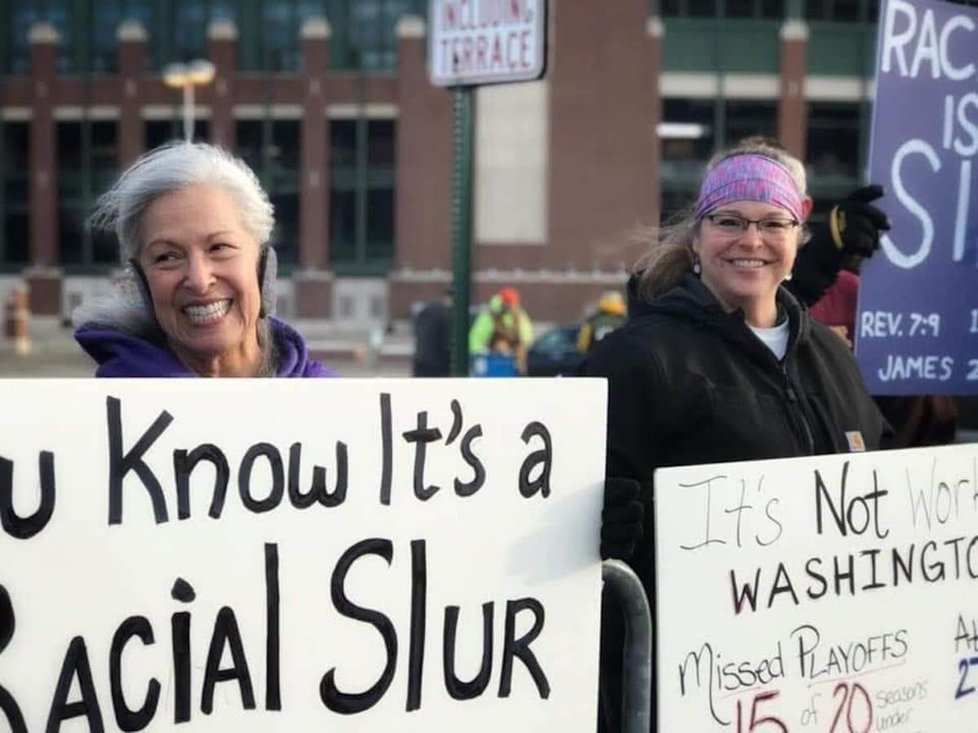 Barb Munson (left) holds a sign outside Lambeau Field denouncing the Washington Football Team's name prior to a decision earlier this year by the team to change it.  (Photo provided by Barb Munson)
