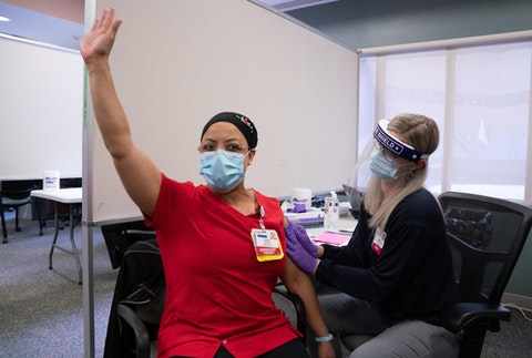 Chestina Schubert raises her hand as she becomes the first person at University Hospital to be vaccinated on Dec. 17. Herd immunity, or vaccinating 70% of state residents, will not be likely by fall unless the federal government increasing vaccine allocation to Wisconsin. (Photo provided by UW Health)