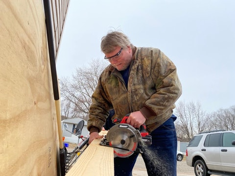 Tom Danielson works Friday on improvements to the mobile home he and his girlfriend, Heidi Oertel, bought two months ago after they were evicted from their previous home. (Photo by Julian Emerson)
