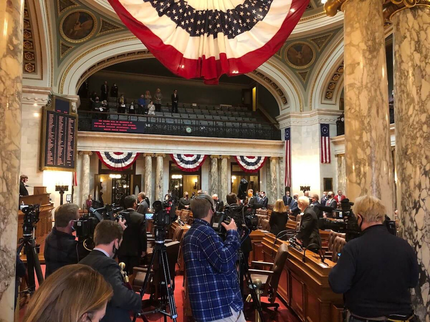 View From the Press Pit – Media members cover the opening day of the Wisconsin Legislature's 2021-2022 session in the Assembly chamber at the state Capitol in Madison. The gallery above, normally filled with families, friends, and staff, is sparse due to COVID-19 restrictions and Democratic members conducting their inaugurals largely online. (Photo by Jessica VanEgeren)
