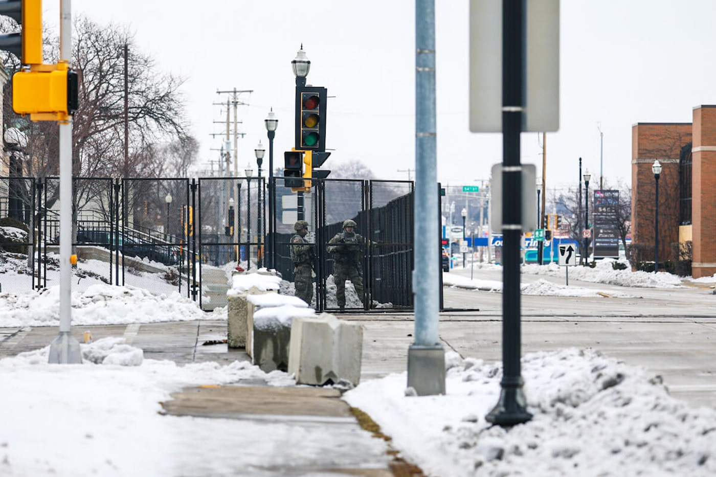 Two members of the Wisconsin National Guard stand behind a fence erected around the Kenosha Courthouse in advance of last week's Kenosha County Attorney General's decision over whether to charge the officer who shot and paralyzed Jacob Blake. The two troops were among 500 activated by Gov. Tony Evers in advance of the decision. (Photo by Samer Ghani)
