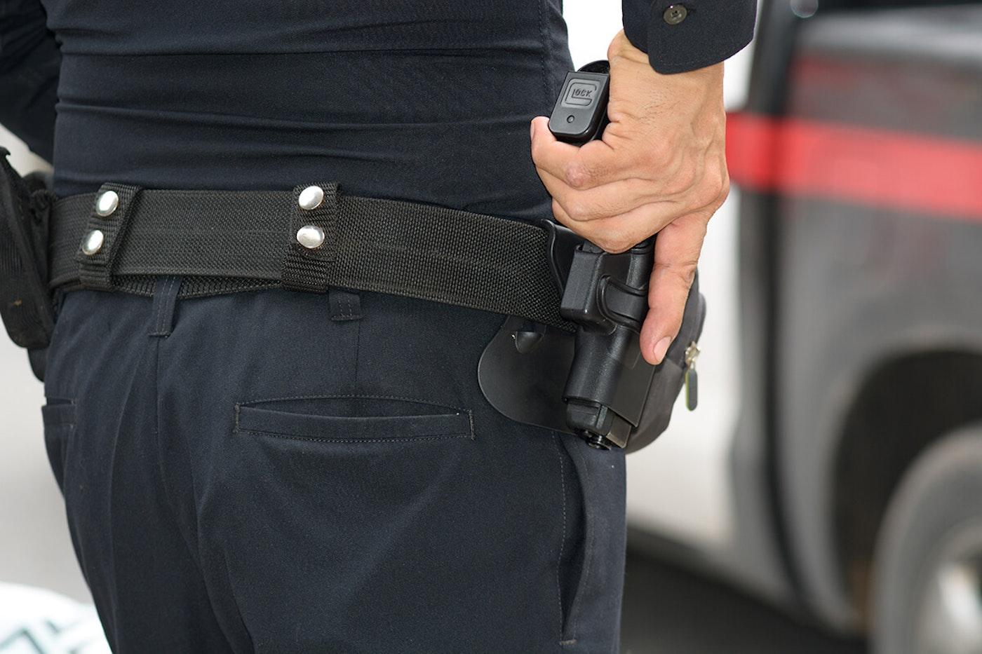 A police officer draws a gun