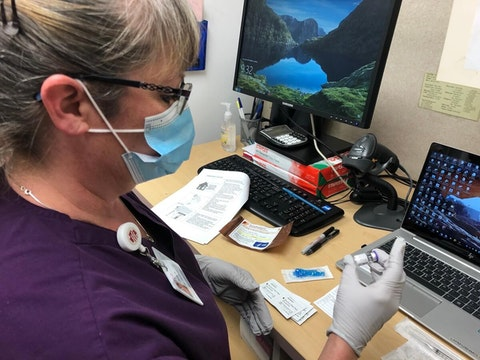 Dana Hanson, assistant operations manager at Marshfield Medical Center-Eau Claire, holds a vial of COVID-19 vaccine in preparation for giving out shots to fellow healthcare workers in the first group of recipients. (Photo courtesy of Marshfield Clinic.)