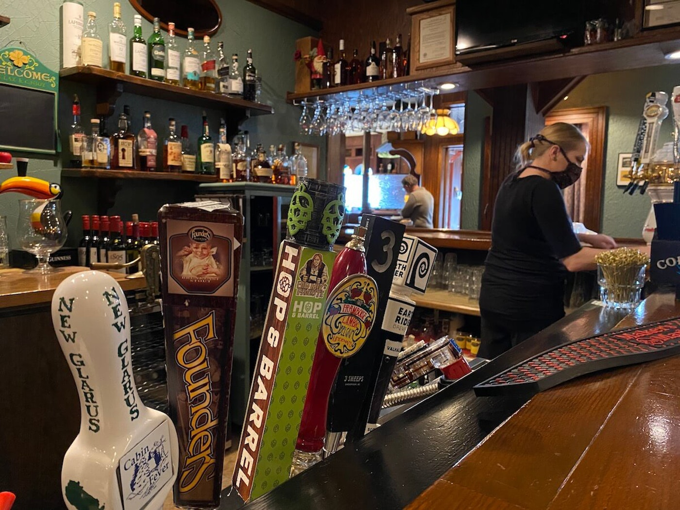 Ashley Deetz cleans the bar area at Houligans Steak & Seafood Pub in downtown Eau Claire Thursday afternoon before the restaurant opened. People working at restaurants, taverns and other service sector jobs have been among the hardest hit financially by the ongoing coronavirus pandemic. (Photo by Julian Emerson)