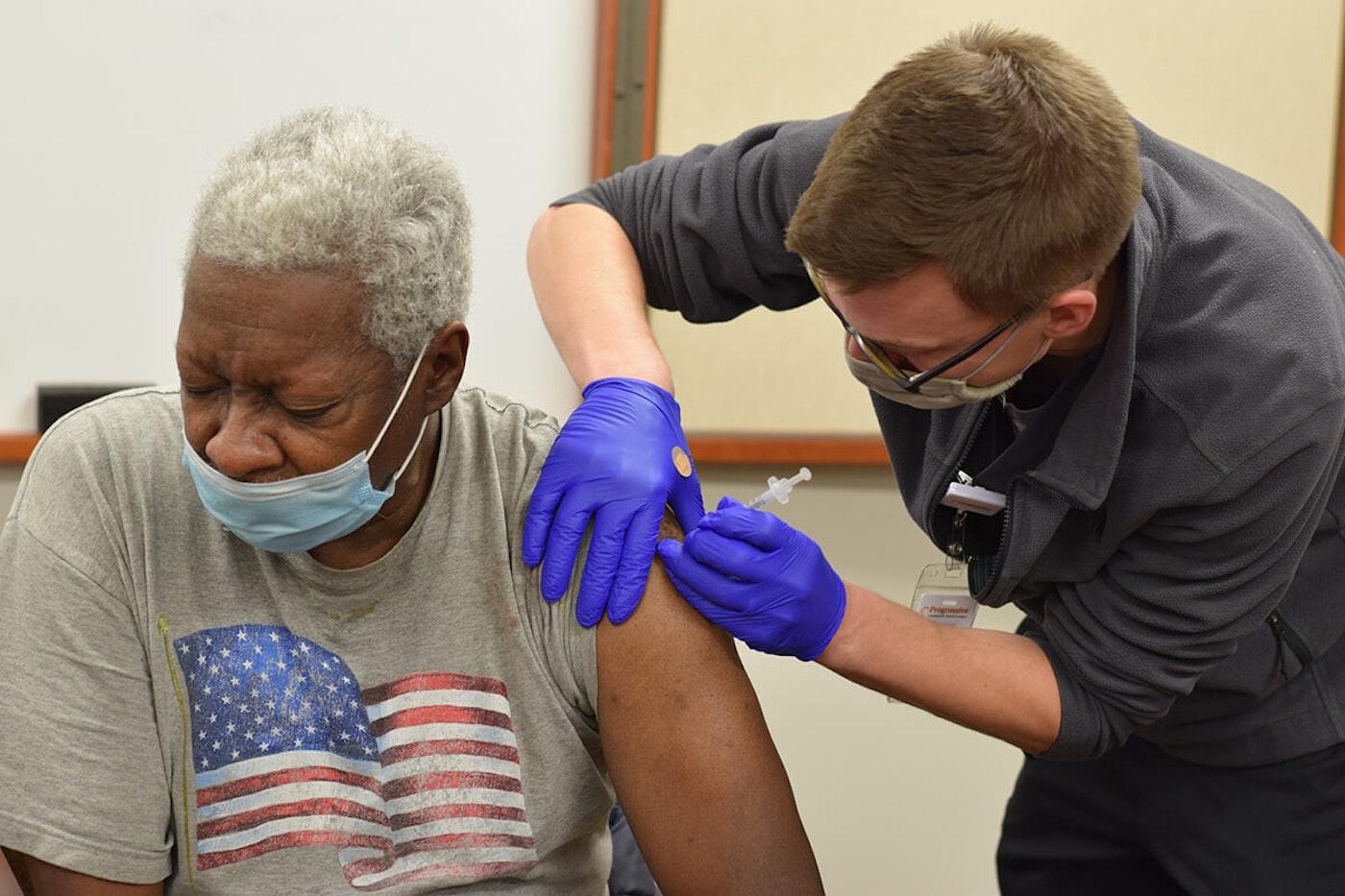Ted Crutcher, 70, of Milwaukee, gets a dose of Pfizer's COVID-19 vaccine Feb. 4 from Jordan Bretzmann, a nurse at Progressive Community Health Centers. (Photo by Jonathon Sadowski)