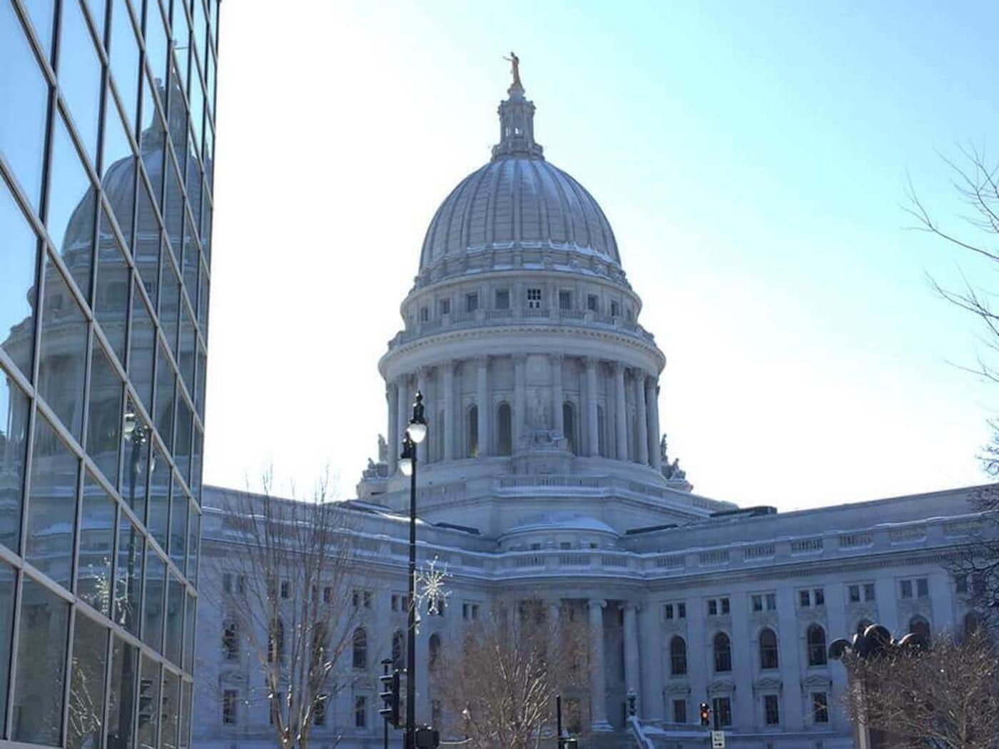 The state Capitol in Madison is reflected off the windows of an office building across the street. (Photo by Julian Emerson)