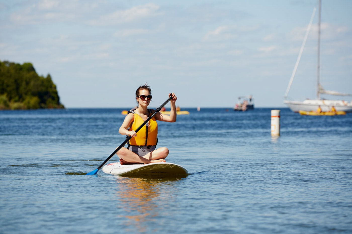 A woman paddle boards in Peninsula State Park in Door County. The county's tourism bureau expects a busy Memorial Day weekend as people begin to travel again after a year of staying put during the pandemic. (Photo courtesy of John Nienhuis/Destination Door County)