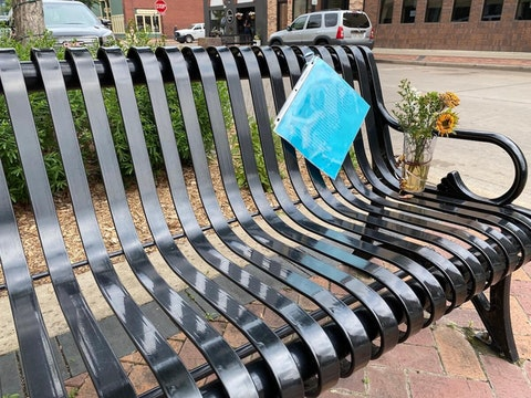 Flowers and a poem are left on a bench in memory of Marilyn Roeber, a homeless woman who often occupied the bench in downtown Eau Claire. Roeber, 66, was found dead on the bench last week. (Photo by Julian Emerson)