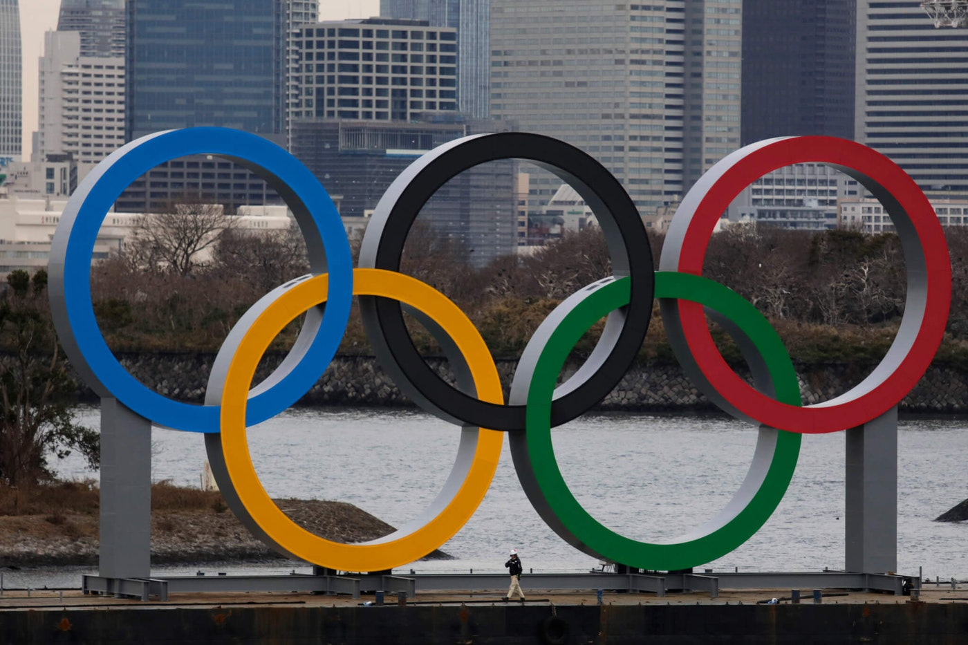 A worker is dwarfed by the Olympics Rings on a barge Friday, Jan. 17, 2020, in the Odaiba district of Tokyo. (AP Photo/Jae C. Hong)