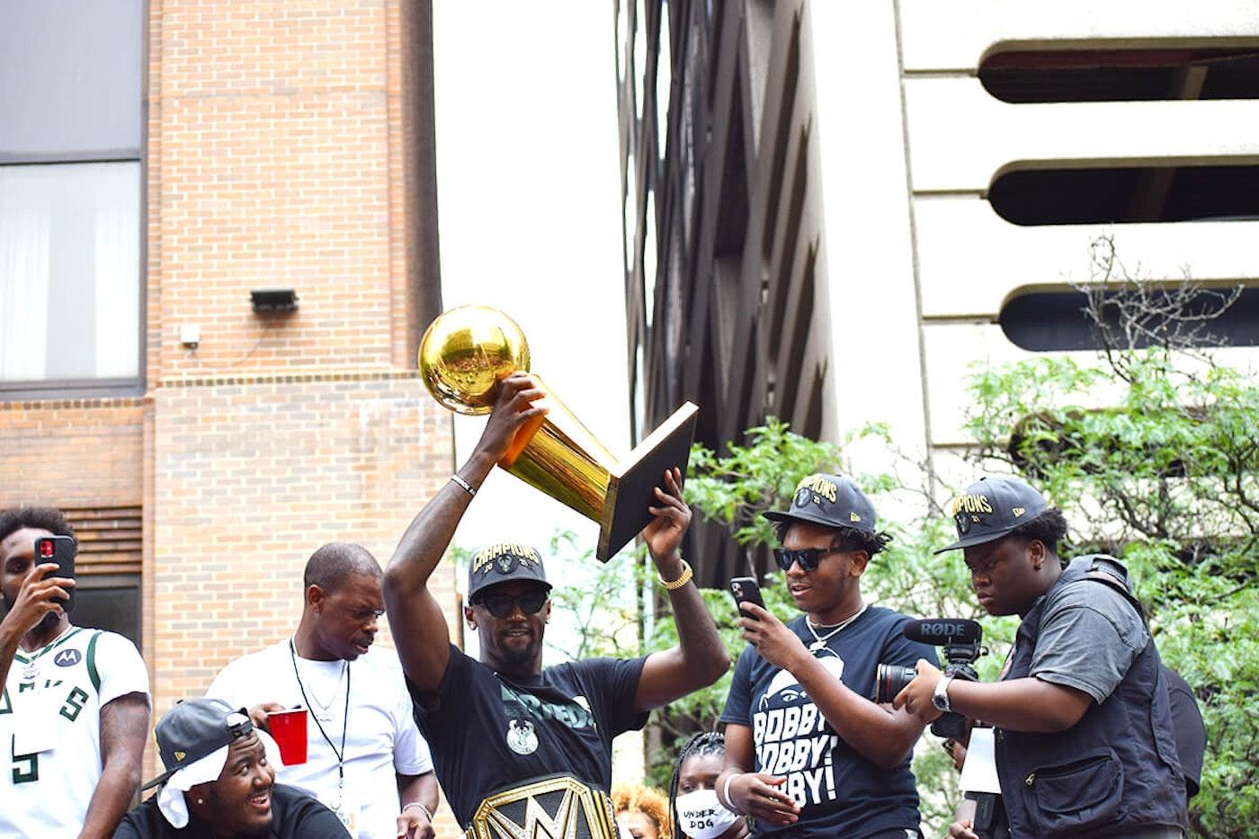 Milwaukee Bucks fan favorite Bobby Portis hoists the Bucks' championship trophy over his head during the team's championship parade in downtown Milwaukee. (Photo by Jonathon Sadowski)