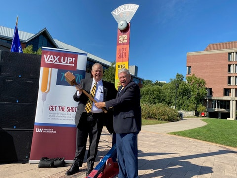 """UW System Interim President Tommy Thompson, right, and UW-Eau Claire Chancellor James Schmidt pose after using a hammer to ring the bell on a """"Smash COVID"""" carnival game during an event at the university Monday to promote students being vaccinated against the virus. (Photo by Julian Emerson)"""