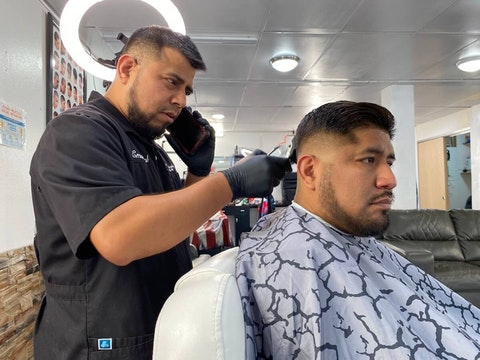 Emanuel Montalvo cuts Aaron Feria's hair on Oct. 12 at The Lounge Barbershop in Arcadia. The barbershop is one of a growing number of Latino-owned businesses in the Trempealeau County city that is home to a fast-growing Latino population. (Photo by Julian Emerson)