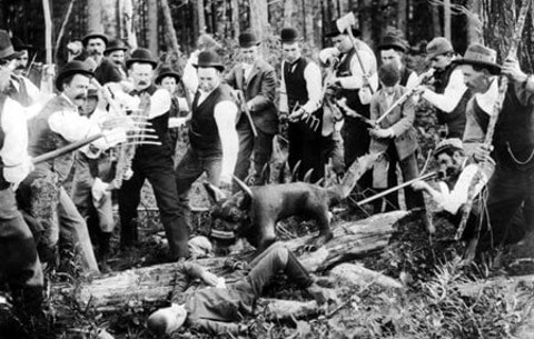 """Lumberjacks stand around the remains of a purported """"hodag"""" in this    1893 photo."""
