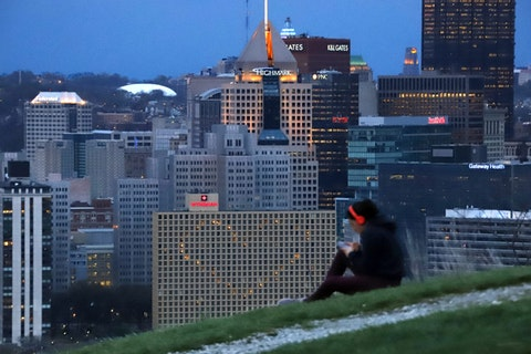 A woman works out on Mt. Washington overlooking the skyline of Pittsburgh that is lit in an Illumination Ovation of thanks and love from Pittsburgh to honor medical, health care and every other kind of essential worker still on the job, Tuesday, April 14, 2020. (AP Photo/Gene J. Puskar)