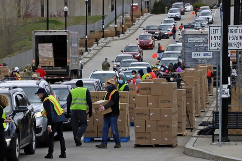 Boxes of food are distributed by the Greater Pittsburgh Community Food Bank, at a drive thru distribution near PPG Arena in downtown Pittsburgh, Friday, April 10, 2020. (AP Photo/Gene J. Puskar)