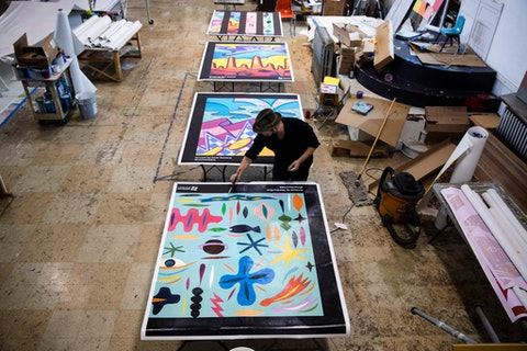 In this Monday, May 4, 2020 photo Ben Volta applies a protective coating on posters destined to be installed on boarded up business in Philadelphia. (AP Photo/Matt Rourke)