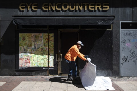 A worker folds up a tarp after attaching a poster to a shuttered business in Philadelphia, Monday, May 4, 2020. The Center City District and Mural Arts Philadelphia posted the original works on multiple locations in an effort to enhance the neighborhood awash with business shuttered to help curb the spread of coronavirus. (AP Photo/Matt Rourke)