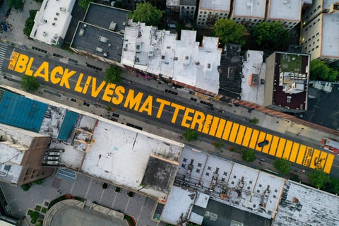 """In this June 15, 2020, file photo, a giant """"BLACK LIVES MATTER"""" sign is painted in orange on Fulton Street, Monday, June 15, 2020, in the Brooklyn borough of New York. (AP Photo/John Minchillo, File)"""