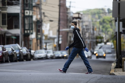 A person wearing a protective face mask as a precaution against the coronavirus walks in Allentown, Pa., Tuesday, May 12, 2020. (AP Photo/Matt Rourke)