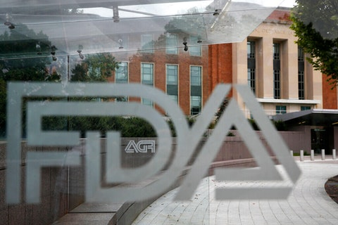 """The U.S. Food and Drug Administration building behind FDA logos at a bus stop on the agency's campus in Silver Spring, Md.  In a report to Congress and an accompanying """"playbook"""" for states and localities, key federal health agencies and the Defense Department sketched out complex plans for a vaccination campaign to begin gradually early next year or later in 2020, eventually ramping up to reach any American who wants a shot. (AP Photo/Jacquelyn Martin, File)"""