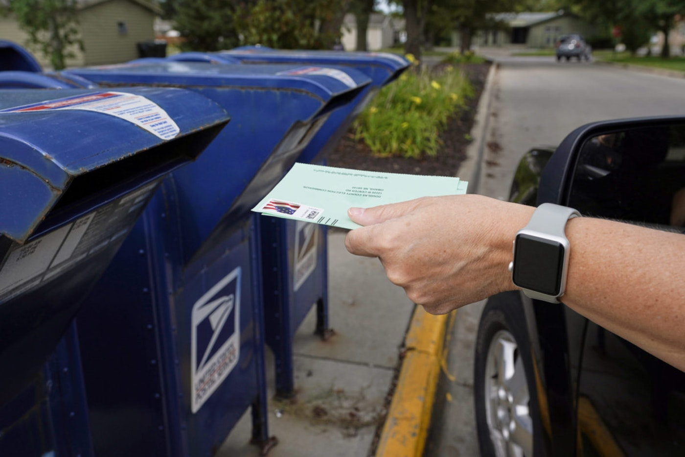 In this Tuesday, Aug. 18, 2020, file photo, a person drops applications for mail-in-ballots into a mailbox in Omaha, Neb. Data obtained by The Associated Press shows Postal Service districts across the nation are missing the agency's own standards for on-time delivery as millions of Americans prepare to vote by mail. (AP Photo/Nati Harnik, File)