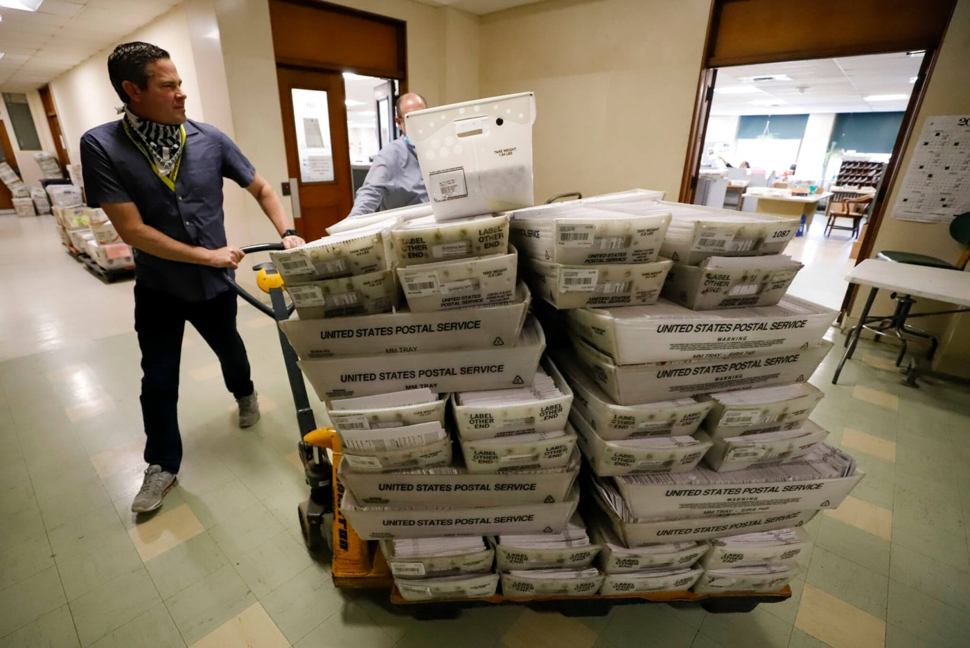 Chet Harhut, deputy manager, of the Allegheny County Division of Elections, wheels a dolly loaded with mail-in ballots, at the division of elections offices in downtown Pittsburgh Wednesday, May 27, 2020. The once-delayed Jun 2 Pennsylvania primary was a first run for some new paper-record voting systems and the inaugural use of newly legalized mail-in ballots. (AP Photo/Gene J. Puskar)