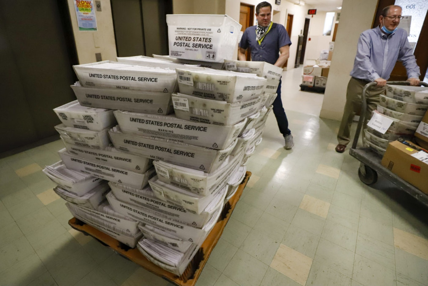 Chet Harhut, left, deputy manager, and David Voye, right, division manager of the Allegheny County Division of Elections, take receipt of a dolly loaded with mail-in ballots, at the division of elections offices in downtown Pittsburgh Wednesday, May 27, 2020. The June 2 Pennsylvania primary was a first run for some new paper-record voting systems and the inaugural use of newly legalized mail-in ballots. (AP Photo/Gene J. Puskar)