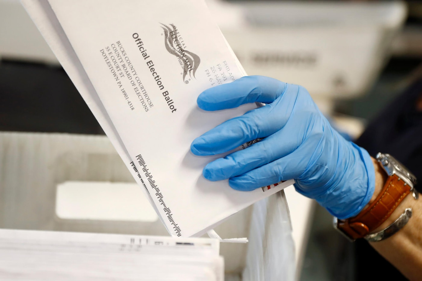 In this May 27, 2020 file photo, a worker processes mail-in ballots at the Bucks County Board of Elections office prior to the primary election in Doylestown, Pa. The counting from Pennsylvania's first foray into mass voting by mail took more than a week. (AP Photo/Matt Slocum, File)