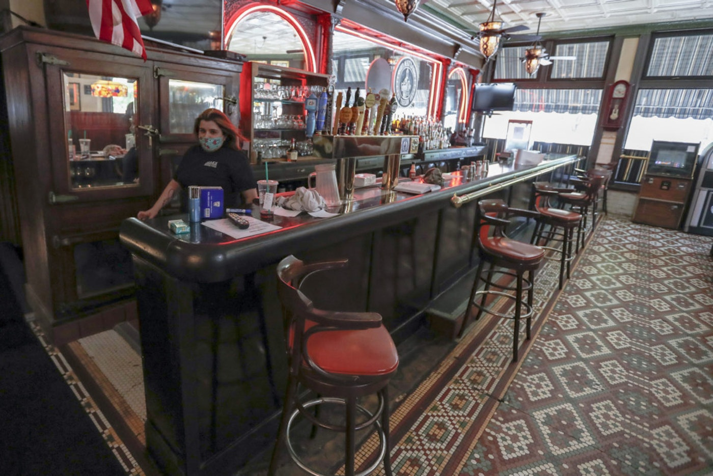 Bartender Sara Kennely walks behind the bar as preparations, like spacing out the barstools, are underway for patrons to dine inside, Thursday, June 4, 2020, at Max's Allegheny Tavern on Pittsburgh's North Side. (AP Photo/Keith Srakocic)
