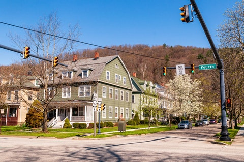 An old house with row houses next to it at the corner of 4th and Hickory streets in Warren, Pa., on a sunny spring day. (Shutterstock Photo/woodsnorthphoto)