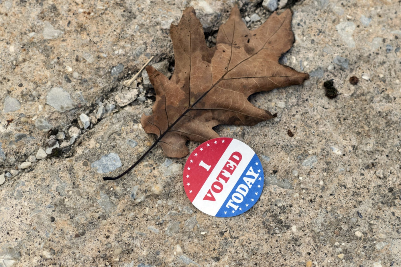 A discarded voting sticker lies on the ground at a satellite election office at Overbrook High School on Thursday, Oct. 1, 2020, in Philadelphia. (AP Photo/Laurence Kesterson)