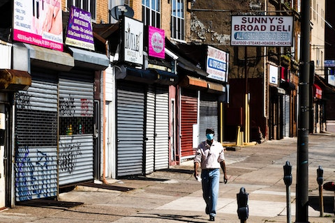 A person wearing a protective mask as a precaution against the coronavirus walks past stuttered businesses in Philadelphia, Thursday, May 7, 2020. (AP Photo/Matt Rourke)