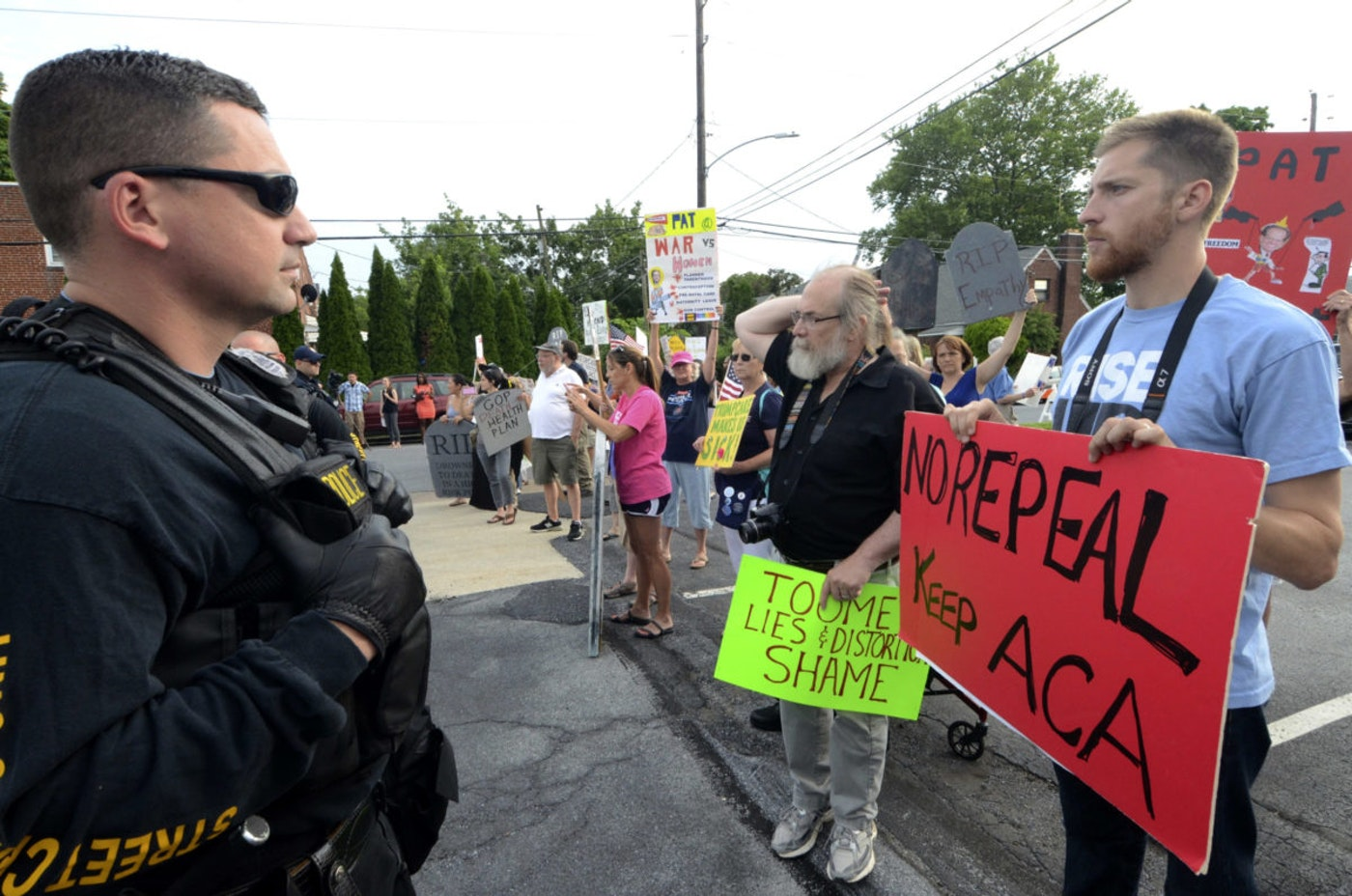 Watched by police, protesters await the arrival of Pennsylvania's US Sen. Pat Toomey outside the studios of WHTM-TV, Wednesday, July 5, 2017 in Harrisburg, Pa. (AP Photo/Marc Levy)