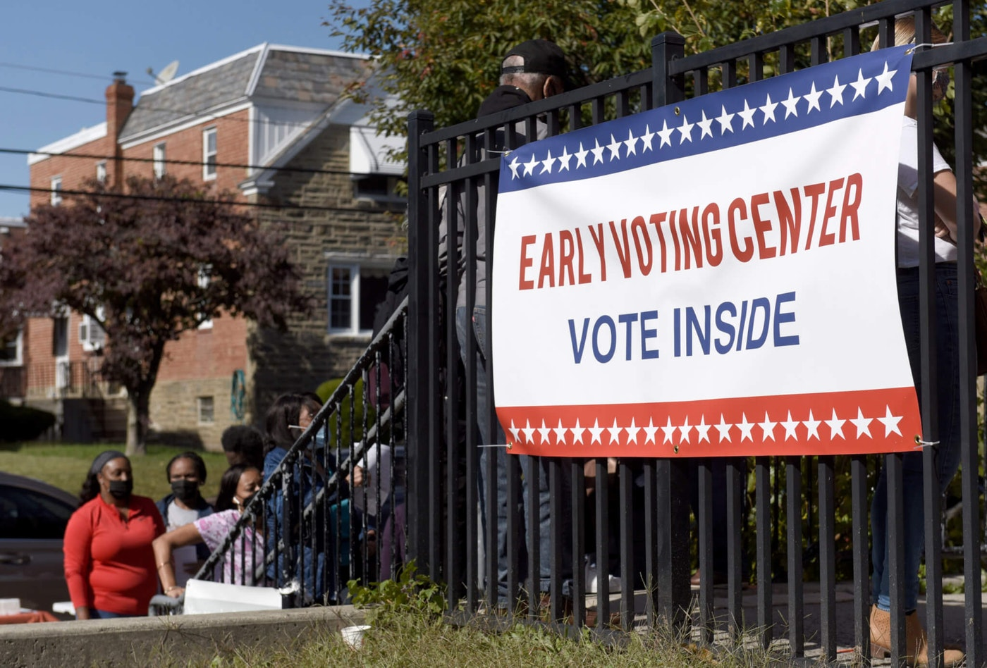 Voters line up at an early voting satellite location at the Anne B. Day elementary school, Thursday, Oct. 15, 2020, in Philadelphia. (AP Photo/Michael Perez)