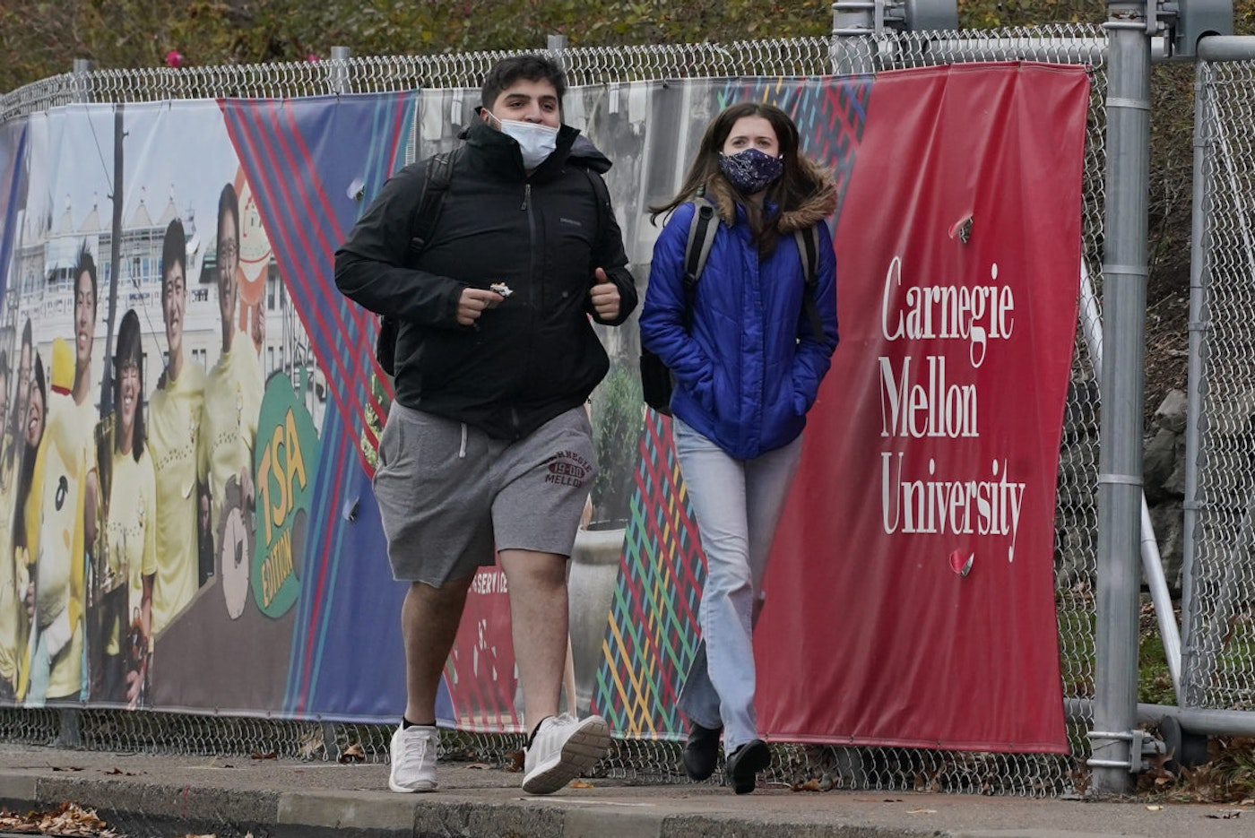 A man and a woman wearing masks walk near the campus of Carnegie Mellon University, in the Oakland neighborhood of Pittsburgh on Tuesday, Nov. 17, 2020. Pennsylvania is strengthening its mask mandate and will require out-of-state travelers to test negative for the coronavirus before arrival. The state health secretary, Dr. Rachel Levine, said the new measures are in response to a sharp increase in infections and hospitalizations. She said Tuesday that masks are now required indoors wherever people from different households are gathered—even if they are physically distant. Like the rest of the nation, Pennsylvania has seen coronavirus infections explode in recent weeks.(AP Photo/Gene J. Puskar)
