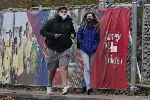 A man and a woman wearing masks walk near the campus of Carnegie Mellon University, in the Oakland neighborhood of Pittsburgh on Tuesday, Nov. 17, 2020. Pennsylvania is strengthening its mask mandate and will require out-of-state travelers to test negative for the coronavirus before arrival. The state health secretary, Dr. Rachel Levine, said the new measures are in response to a sharp increase in infections and hospitalizations. She said Tuesday that masks are now required indoors wherever people from different households are gathered—even if they are physically distant. Like the rest of the nation, Pennsylvania has seen coronavirus infections explode in recent weeks. (AP Photo/Gene J. Puskar)