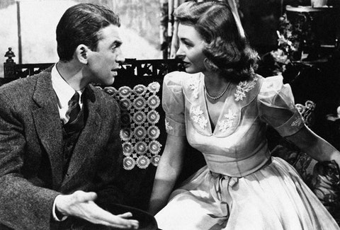 """George Bailey (Jimmy Stewart) explains things to Mary Hatch (Donna Reed) in """"It's a Wonderful Life"""" in 1946. (AP Photo)"""
