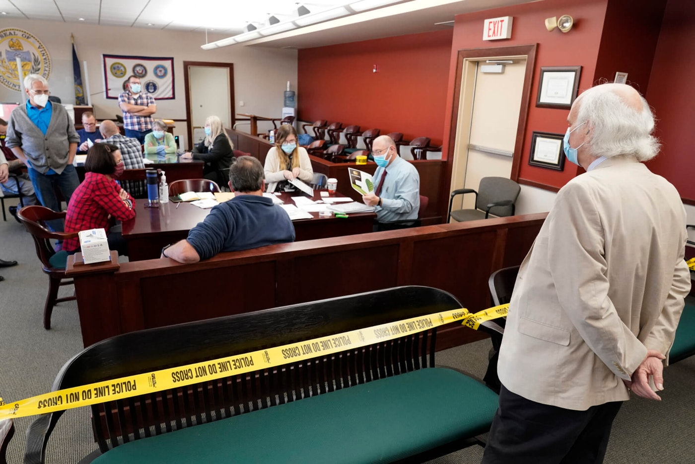 In this Nov. 6, 2020, file photo, an observer watches as Luzerne County workers canvas ballots that arrived between the closure of the polls and 5 p.m. Nov. 6, as vote counting in the general election continues in Wilkes-Barre, Pa. (AP Photo/Mary Altaffer, File)