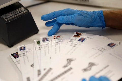 A worker processes mail-in ballots at the Bucks County Board of Elections office prior to the primary election, Wednesday, May 27, 2020 in Doylestown, Pa. (AP Photo/Matt Slocum)