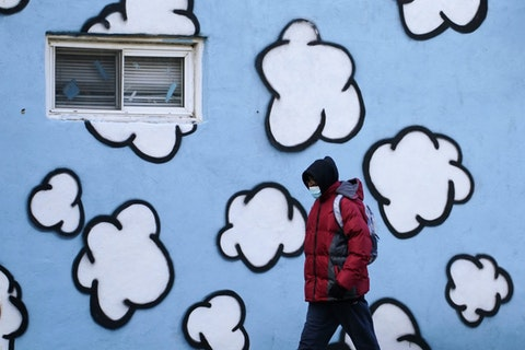 A person wearing a face mask to protect against the spread of the coronavirus walks along Market Street, Dec. 8, 2020, in West Philadelphia. (AP Photo/Matt Slocum)