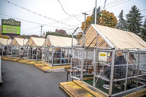 In this Oct. 20, 2020, file photo, people have dinner in greenhouses used for outdoor dining amid the coronavirus pandemic at North Park Lounge in McCandless, Allegheny County. An increasing number of governors and mayors are imposing restrictions ahead of Thanksgiving for fear that holiday travel and family gatherings will only worsen the record-breaking, coast-to-coast resurgence of the coronavirus. (Alexandra Wimley/Pittsburgh Post-Gazette via AP, File)