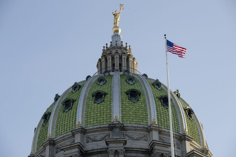 In this Jan. 15, 2019, file photo an America flag flies at the Pennsylvania Capitol building in Harrisburg. (AP Photo/Matt Rourke, File)